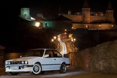 Kamenetz-Podolskiy, Ukraine - April 13, 2012. BMW 325 E 30, whit. E car in the old town, classic car, lowrider, lowride car in the lights of the night city Royalty Free Stock Photos