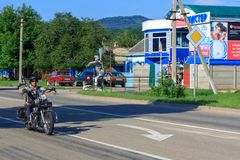 A lone biker rides a motorcycle on the road on a summer day in the village of Kamennomostsky stock photo