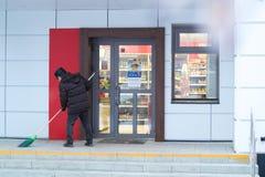 Kamensk-Uralsky, Россия, 10-ое февраля 2018: Привратник подметает крылечко магазина, работая пенсионер Стоковые Фото