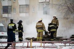 Kamensk-Uralsky, Russland, am 10. Februar 2018: Feuerwehrmänner auf dem Standort eines Feuers, Rauch von gut herein, das ein Feue Stockbild