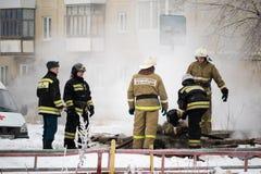 Kamensk-Uralsky, Russland, am 10. Februar 2018: Feuerwehrmänner beseitigen den Brandherd auf dem Hintergrund eines mehrstöckigen  Lizenzfreies Stockfoto