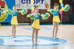 Young cheerleaders perform at the city cheerleading championship. Kamenskoye, Ukraine - March 9, 2017: Championship of the city of Kamenskoye in cheerleading Royalty Free Stock Images