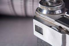 Kamera auf dem Hintergrund einer Rolle des negativ Film Lizenzfreie Stockfotos