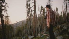 Kamera befördert den jungen männlichen kaukasischen Journalisten der Runde, der mit Kamera auf Waldsonnenuntergang an der Yosemit stock video