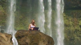 Kamera bewegt sich auf Dame mit Laptop durch schäumenden Wasserfall stock video