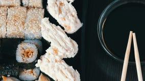 Kamera bewegt sich nach links Stilvoll gelegte Sushi stellten auf einen schwarzen hölzernen Hintergrund nahe bei Sojasoße und chi stock video