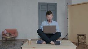 Kamera bewegt sich um kreativen Geschäftsmann während er auf dem Tisch sitzend im Lotussitz mit Laptop und dem Arbeiten stock footage