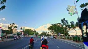 Kamera bewegt sich unter Rollern entlang Straße hinter Baum-Bussen stock video