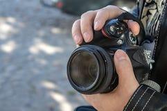 Kamera in den Händen einer Fotograf ` s Nahaufnahme lizenzfreie stockbilder