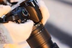 Kamera in den Händen eines Mädchens im Winterwald stockfoto