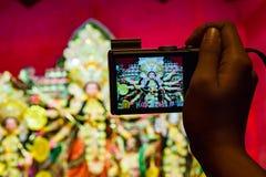 Kamera in der Hand, die Foto von durga Idol in der flachen Schärfentiefe des Hintergrundes macht Stockfotografie