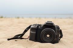 Kamera, die auf dem Sand auf dem Strand liegt Stockbilder
