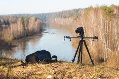 Kamera, die auf Stativ an der Morgenwaldflusslandschaft, Frühling in Ural steht Lizenzfreie Stockbilder