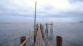 Kamera durch Bambusbrücke in Richtung zum schlammigen Meer stock footage