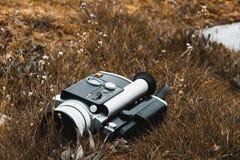 Kamera för 8 film för gammal tappning som toppen ligger på dött gräs royaltyfria bilder