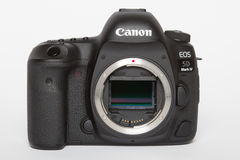 Kamera för foto för profesional DSLR för dropp för fläck för Canon EOS 5D på vit reflekterande bakgrund Arkivfoton
