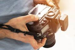 Kamera för reflex Digital för enkel lins i manliga händer Fotografskyttehänder tätt upp Manfotografen gör foto Manligt handH royaltyfri fotografi