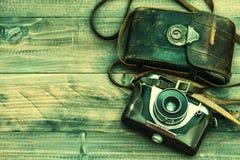 Kamera för tappningfilmfoto med läderpåsen på träbakgrund Arkivfoton