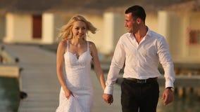 Kamera folgt Braut und Bräutigam, während sie zur Zeremonie nach Uferzone nahe Bungalows auf Brücke am Luxus-Resort an gehen stock footage