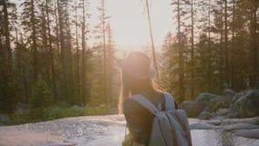 Kamera folgt dem aufgeregten touristischen Mädchen, das oben im tiefen Holz, Weg zu überraschendem Strom an der Sonnenuntergang Y stock video footage