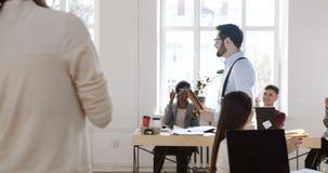 Kamera folgt dem glücklichen jungen lächelnden erfolgreichen Geschäftsmann, der modernes Büro betritt, Kollegen klatschen, um ihn stock footage