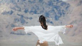 Kamera folgt der jungen glücklichen Frau, die mit den Armen geht, die offen sind und dem Haar, das im starken Wind am sonnigen Sa stock footage
