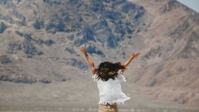 Kamera folgt der jungen glücklichen freien Frau, die mit den Armen springt und spinnt, die offen sind und dem fliegenden Haar, da stock video footage