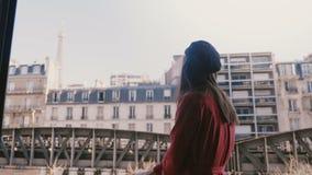 Kamera folgt der jungen glücklichen touristischen Frau, die an sonnigem Paris-Balkon lächelt und zeigt auf epische Eiffelturmansi stock video