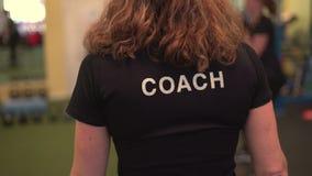 Kamera folgt einem Eignungslehrertrainer durch eine beschäftigte Turnhalle
