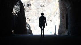 Kamera folgt einem Frauenschattenbild, das durch dunklen Tunnel in Richtung zum Licht geht, das Arme in einer Luft anhebt stock video footage