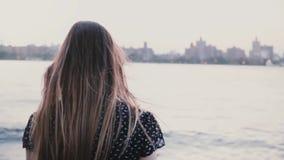 Kamera folgt Mädchen im schwarzen Kleid, das unten zum großen Flussufer, die Uhr laufen gelassen wird, die New- Yorksonnenunterga stock video footage