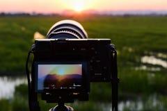 Kamera i äng och solnedgånghimmel Arkivfoton