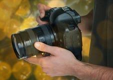 kamera na fotograf rękach Zielony i żółty bokeh tło nasunięcie i Zdjęcia Royalty Free