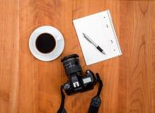 Kamera, Notizblock mit Stift und Kaffee auf Holztisch Lizenzfreie Stockfotografie