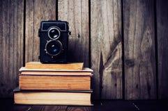 Kamera och en bunt av böcker Arkivfoto