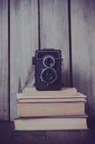 Kamera och en bunt av böcker Arkivbild