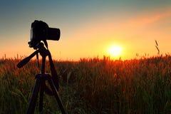 Kamera och tripod på solnedgånghimmelbakgrund Royaltyfria Bilder
