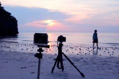 Kamera och tripod på stranden med en bakgrundsbild av flickan Fotografering för Bildbyråer