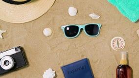 Kamera, pass, solglasögon och hatt på strandsand lager videofilmer