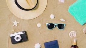 Kamera, pass, solglasögon och hatt på strandsand arkivfilmer