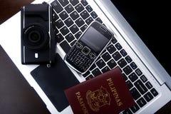 Kamera, Pass und Mobiltelefon auf einer Laptop-Computer Lizenzfreie Stockfotos