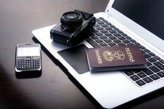 Kamera, Pass und Mobiltelefon auf einer Laptop-Computer Lizenzfreies Stockfoto