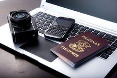 Kamera, Pass und Mobiltelefon auf einer Laptop-Computer Lizenzfreie Stockbilder