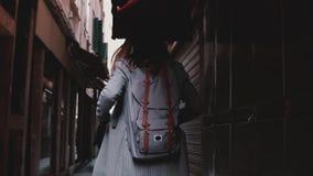 Kamera podąża eleganckiego bizneswomanu z plecaka odprowadzeniem wzdłuż ciemnej antycznej ulicy w Wenecja, Włochy zwolnione tempo zbiory wideo