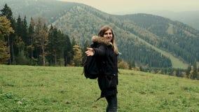 Kamera podąża młoda dziewczyna wycieczkowicza bieg przez doliny góra krajobraz, doskakiwanie, ono uśmiecha się, podwyżek ręki w p zbiory wideo