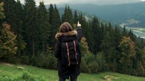 Kamera podąża młoda dziewczyna wycieczkowicza chodzi outdoors i przedstawienie ręki na góra krajobrazie zdjęcie wideo