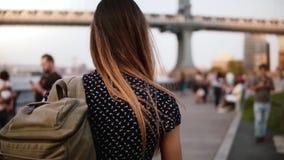 Kamera podąża młodego żeńskiego turysty chodzi wzdłuż pogodnego Brooklyn parka Nowy Jork zwolnionego tempa z plecakiem w okularac zbiory wideo