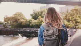 Kamera podąża młodego żeńskiego turysty z plecaka odprowadzeniem wzdłuż pogodnego Brooklyn parka bulwaru rzecznego zwolnionego te zbiory