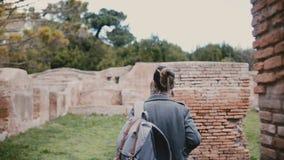 Kamera podąża młodej kobiety z plecaka odprowadzeniem wśród antycznych czerwonej cegły ruin w Ostia Antica, Włochy, na urlopowej  zdjęcie wideo