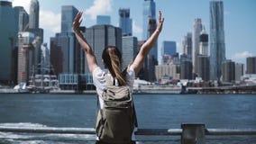 Kamera podąża młodej szczęśliwej podróżnik dziewczyny z plecakiem, skacze z rękami szeroko otwarty przy Manhattan linią horyzontu zdjęcie wideo